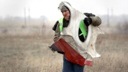 A worker removes a piece of MH17 wreckage in eastern Ukraine in November 2014