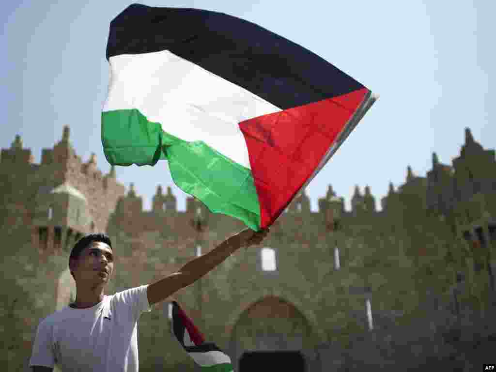 A Palestinian man at Jerusalem's Damascus Gate waves his national flag during a protest on September 21 ahead of his country's bid for statehood recognition at the United Nations in New York. (Photo taken by Marco Longari for AFP)