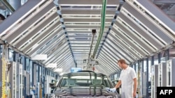 """A Volkswagen employee polishes a VW Phaeton at the car company's """"transparent"""" factory in Dresden."""