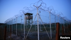Chain link fence and concertina wire surrounds a guard tower within Joint Task Force Guantanamo's Camp Delta at the U.S. naval base in Guantanamo Bay, Cuba.