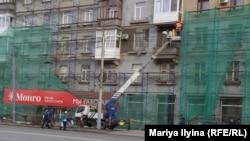 Омбының орталығындағы көпқабатты үйдің сыртын жөндеп жатқан жұмысшылар.
