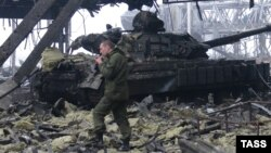 یکی از شبهنظامیان از کنار یک تانک سوخته ارتش اوکراین در فرودگاه دونتسک میگذرد