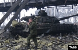 A pro-Russian militants walks past a tank at the Donetsk airport.