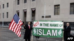 """Demonstrators outside the court in Detroit hold a sign reading """"Not in the name of Islam."""""""
