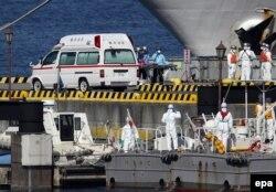Медики швидкої допомоги та берегової охорони Японії в захисному спорядженні готуються до транспортування заражених пасажирів, які перебували на борту круїзного лайнера Diamond Princess, у порту Йокогама, 5 лютого 2020 року