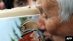 A supporter of the ultranationalist Serbian Radical Party kisses a picture of Ratko Mladic.
