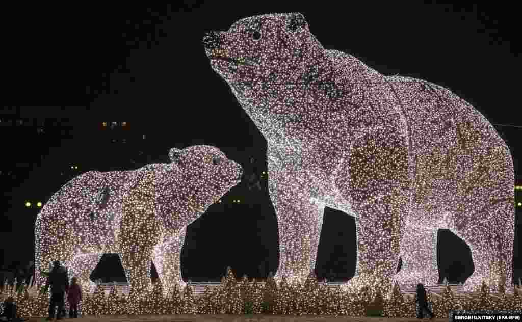 Луѓе покрај огромни светлосни скулптури на поларни мечки инсталирани како дел од украсите за новогодишните и божиќните празници во Москва, на 14 декември 2020 година.