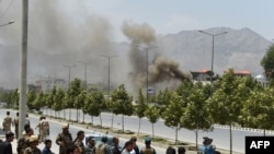 Afghan security personnel and bystanders look on as black smoke billows from the Afghan Parliament building in Kabul on June 22.