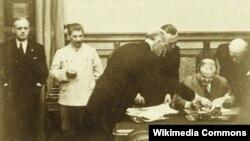 Viaceslav Molotov semnează Tratatul de prietenie dintre URSS și Germania în prezența lui Stalin și a lui Joachim Ribbentrop. Moscova, Kremlin, 23 august 1939.