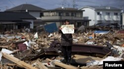 "Japan -- Yasuyoshi Chiba of Japan, has won the first prize People in the News Stories with the ""Aftermath of the tsunami"" series. Chieko Matsukawa shows her daughter's graduation certificate as she finds it in the debris in Higashimatsushima, 03Apr2011"