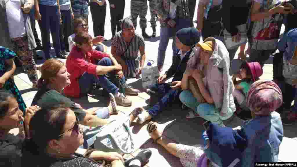 Женщины в окружении полиции ждут выполнения своих требований.