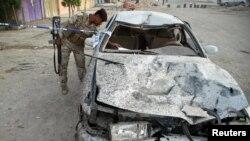 جندي يتفحّص سيارة متضررة بإنفجار البصرة