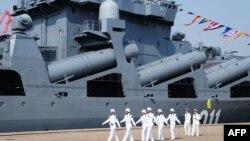 """Китайские моряки маршируют на фоне российского корабля """"Адмирал Виноградов"""". Циндао, 23 апреля 2013 года."""
