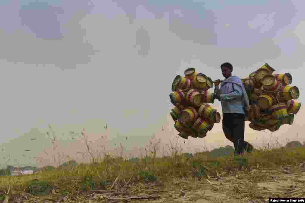 An Indian villager named Dharampal, 37, carries cane baskets for sale on the outskirts of Allahabad. The baskets are sold for 35 rupees (50 U.S. cents) apiece. Dharampal says he earns between 8,000 to 10,000 rupees ($125 to $150) a month. (AP/Rajesh Kumar Singh)
