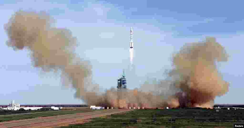 China's Long March 2-F rocket blasts off with three astronauts onboard for a 15-day mission to an experimental space lab in the latest step toward the development of a Chinese space station. (Reuters)