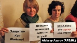 "Активистки держат плакаты против строительства курорта ""Кокжайляу"". Алматы, 11 января 2013 года."