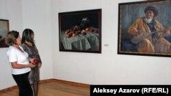 Посетительницы выставки к 80-летию Государственного музея искусств имени Абылхана Кастеева рассматривают полотна Александра Риттиха (1889–1945) «Яблоки» и «Портрет Джамбула». Алматы, 15 сентября 2015 года.