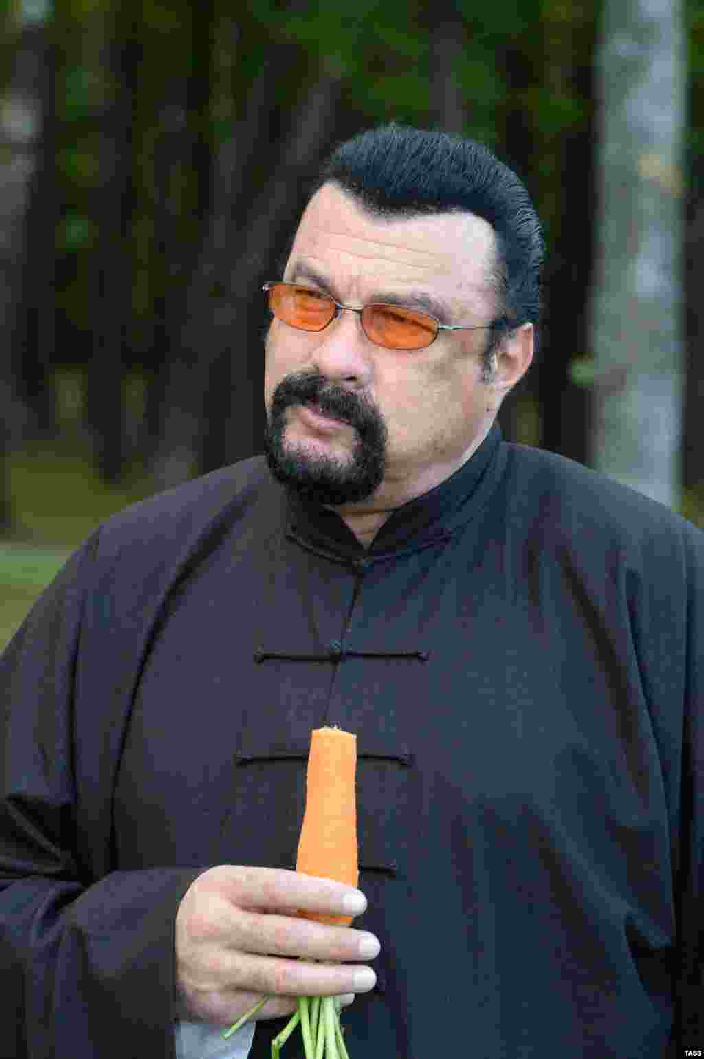 U.S. action star Steven Seagal is seen munching on a homegrown carrot that had been cleaned and peeled for him by Belarusian President Alyaksandr Lukashenka at the president's residence near Minsk. The odd encounter trended heavily on social media. Seagal was in Belarus for talks with a video game developer. (TASS/Andrei Stasevich)