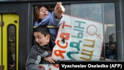 Women gesture from a police van after they were arrested while protesting against gender-based violence to mark International Women's Day in Bishkek on March 8, 2020.
