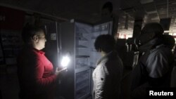 Ukraine, Crimea - An employee (L) speaks with people at an electronics store, with the power turned off inside, in Simferopol, Crimea, November 22, 2015.