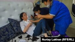 Medics examine Kazakh activist Saule Abildakhanqyzy after she said she was assaulted in Almaty on June 5.