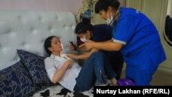 Медики проводят осмотр активистки Сауле Абильдаханкызы. Алматы, 5 июня 2019 года.