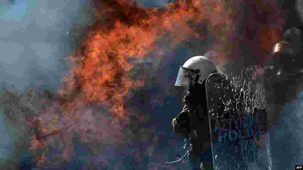 A fire bomb explodes near a riot police squad during clashes with Greek antiausterity demonstrators in Athens on September 26. (AFP/Aris Messinis)