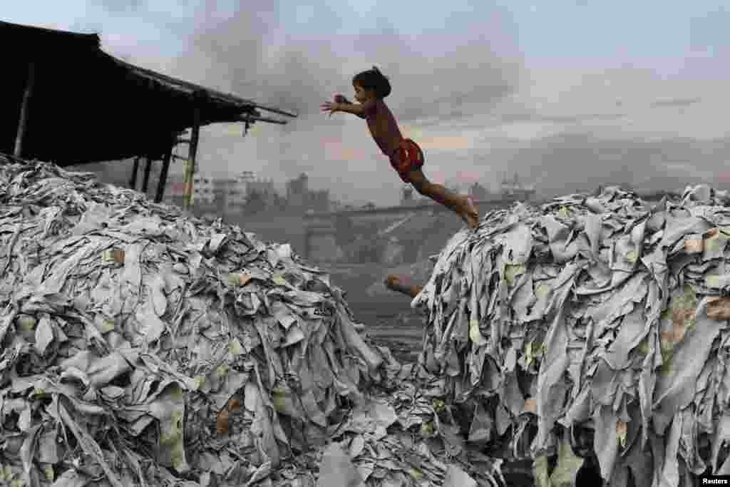A Bangladeshi boy jumps on waste products that are used to make poultry feed as she plays in a tannery in Dhaka.