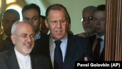 Russian Foreign Minister Sergei Lavrov (center) and Iranian Foreign Minister Mohammad Javad Zarif (left) enter a hall during their meeting in Moscow on April 28.