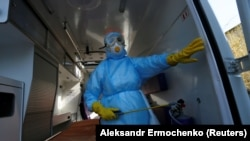 A member of the medical staff sprays disinfectant inside an ambulance at the Vishnevskiy hospital in Donetsk.