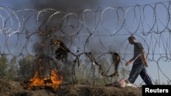 A Hungarian policeman walks past burning clothes belonging to Syrian migrants on a border fence between Serbia and Hungary near the village of Horgos on August 28.