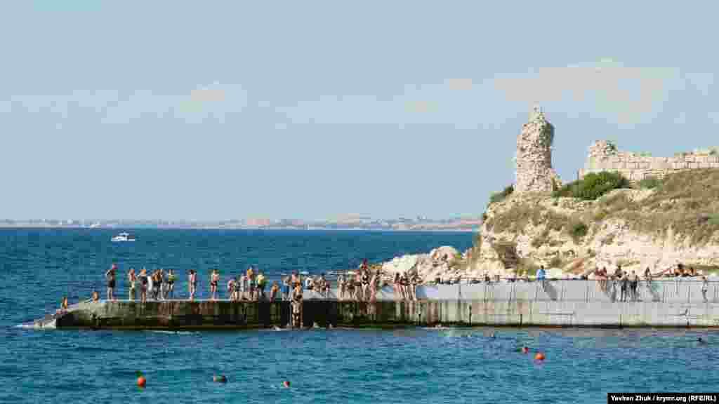 За молом на правой оконечности пляжа – территория музея-заповедника «Херсонес Таврический». Видны развалины древнего полиса