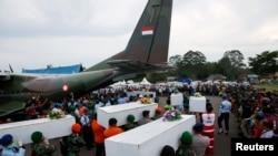 Индонезийские спасатели грузят найденные останки погибших в самолет. 2 января 2015 года.