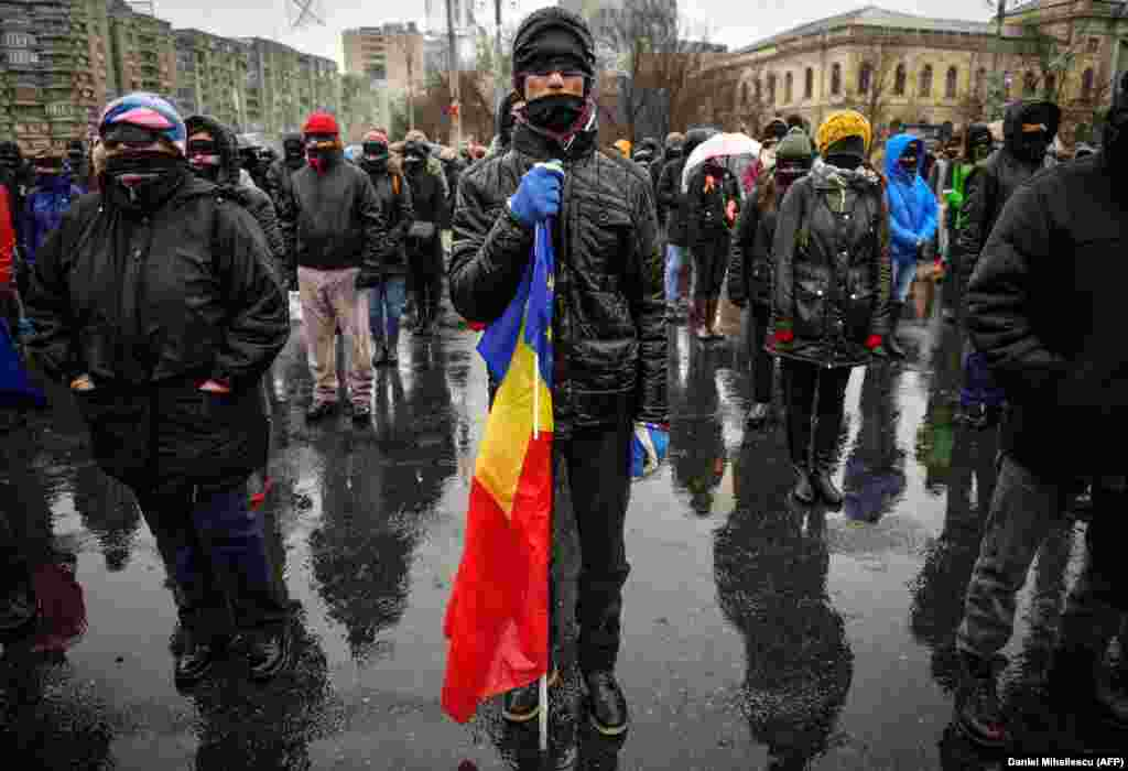 A man holds European and Romanian flags during a protest outside government headquarters in Bucharest against planned changes to the Romania's legal system. (AFP/Daniel Mihailescu)
