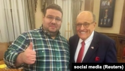 Political consultant Andriy Telizhenko (left) with Rudy Giuliani in Kyiv on December 5.
