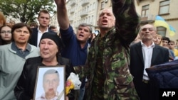 A woman holds a portrait of her dead son, who served in a volunteer battalion, during a rally in front of Ukrainian President Petro Poroshenko's office in Kyiv on August 27.