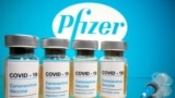 "FILE PHOTO: Vials with a sticker reading, ""COVID-19 / Coronavirus vaccine / Injection only"" and a medical syringe are seen in front of a displayed Pfizer logo in this illustration taken October 31, 2020."
