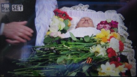 Flowers adorn the coffin of controversial pro-Russian journalist Oles Buzyna at his memorial ceremony in Kyiv on April 19, three days after he was gunned down near his apartment in the capital.