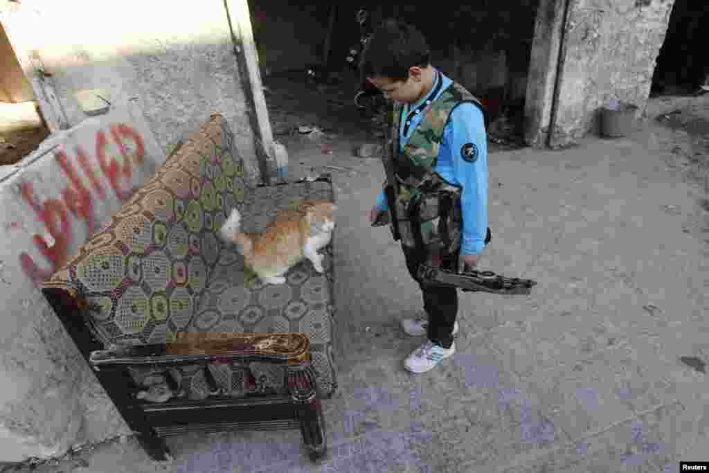 Abboud, 12, plays with a cat while holding his weapon in Aleppo's Sheikh Saeed neighborhood in Syria. (Reuters/Muzaffar Salman)