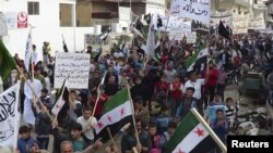 Demonstrators hold opposition flags during a protest against Syria's President Bashar al-Assad, after Friday prayers in Binsh near Idlib on November 2.