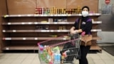 A woman wearing a protective mask walks past empty shelves at a supermarket