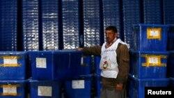 Owganystanyň saýlaw komissiýasynyň işçisi ses berişlik üçin gapyrjaklaryň ýanynda dur, Kabul, 3-nji aprel, 2014.