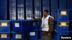 An Afghan Election Commission worker stands by ballot boxes and election material at a warehouse in Kabul. Turnout is expected to be much higher than in 2009.