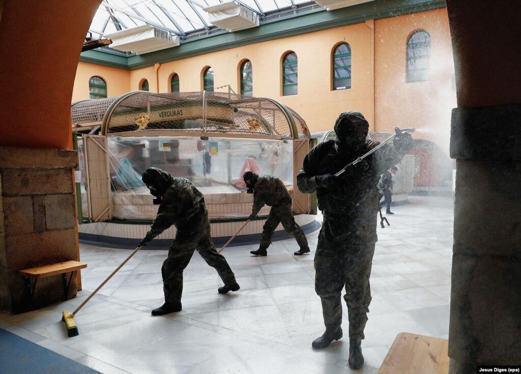 Ushtarët spanjollë duke dezinfektuar një dyqan në Pamplona më 8 prill të vitit 2020.