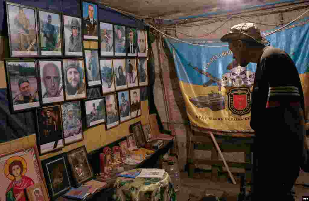 A Ukrainian serviceman looks at portraits of lost friends in a shelter at their position on the front lines near Avdiyivka. (epa/Valeri Kvit)