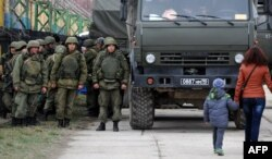 Ресейшіл күштердің қасынан өтіп бара жатқан бала жетектеген әйел. Қырым, Феодосия, 24 наурыз 2014 жыл.