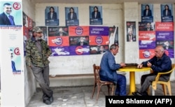 Georgian men play dominoes at a bus stop pasted over with presidential campaign posters in Telavi earlier this week.