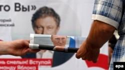 Сторонник «Единой России» раздает газеты с портретом президента Путина у предвыборного плаката партии «Яблоко»