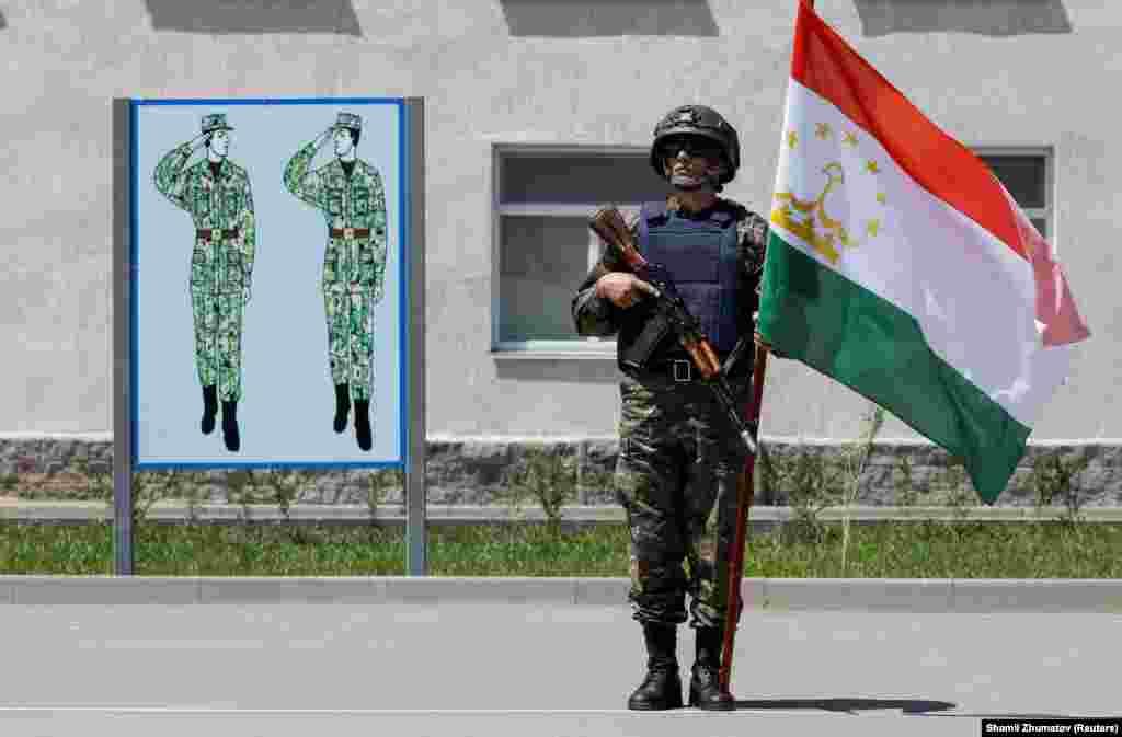 Военнослужащий с флагом Таджикистана.