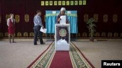 Женщина голосует на президентских выборах в селе Туздыбастау Алматинской области. 26 апреля 2015 года.